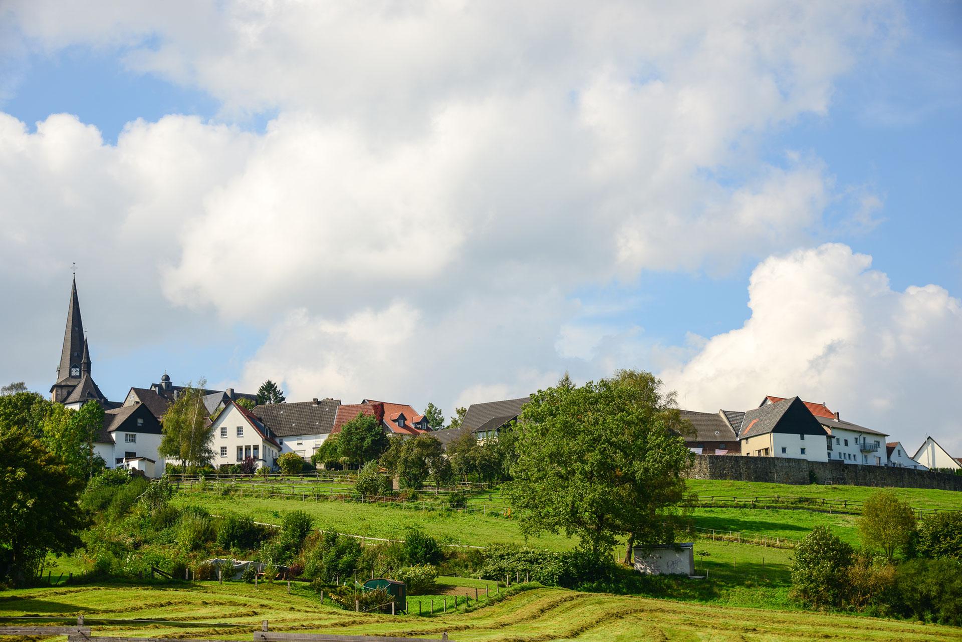 Blick-auf-die-Stadtmauer-von-Kallenhardt-mit-St.Clemens-Kirche-Foto-Zoomfaktor